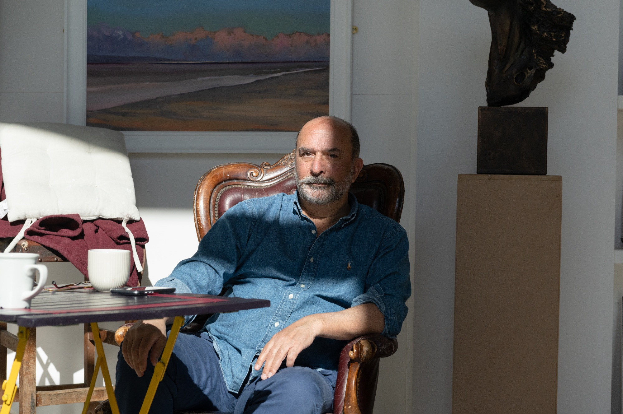 Portrait of a man sitting inside with paintings and sculpture around him