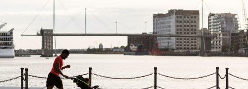 A runner jogging along the docks while pushing a pram