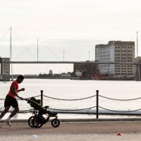 A runner jogging along the docks while pushing a pram