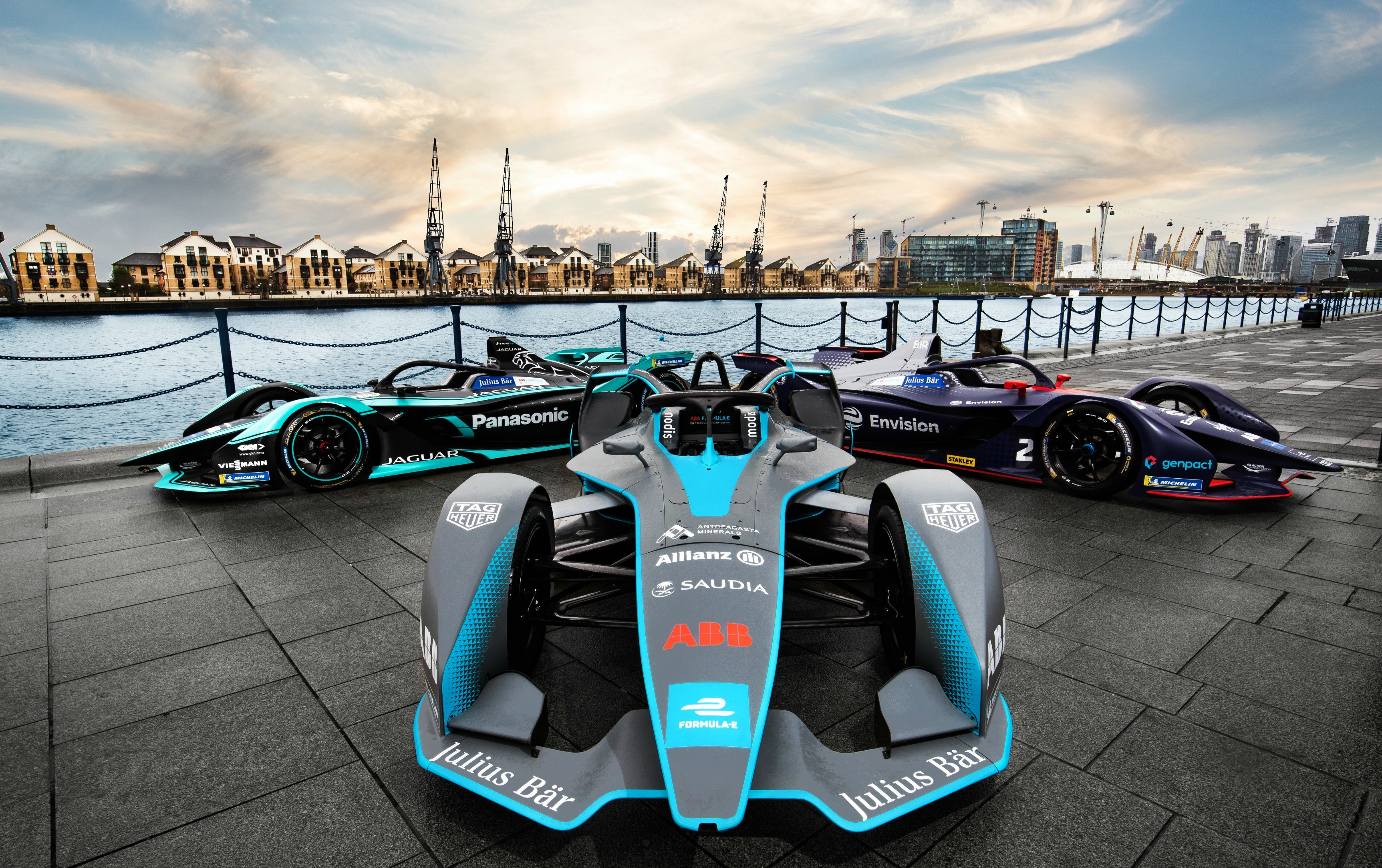 Three Formula E cars on display with the docks in the background