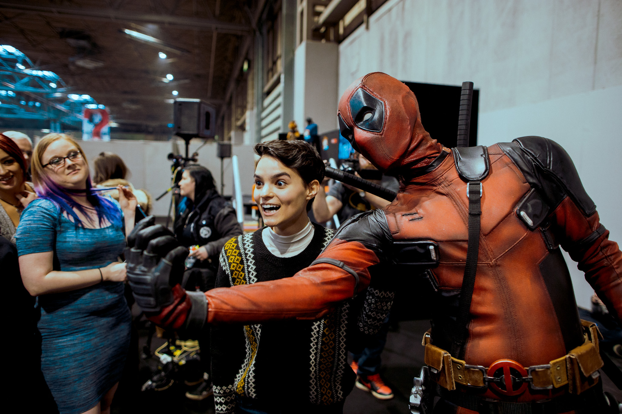 Attendees at Comic Con taking a photo with Deadpool