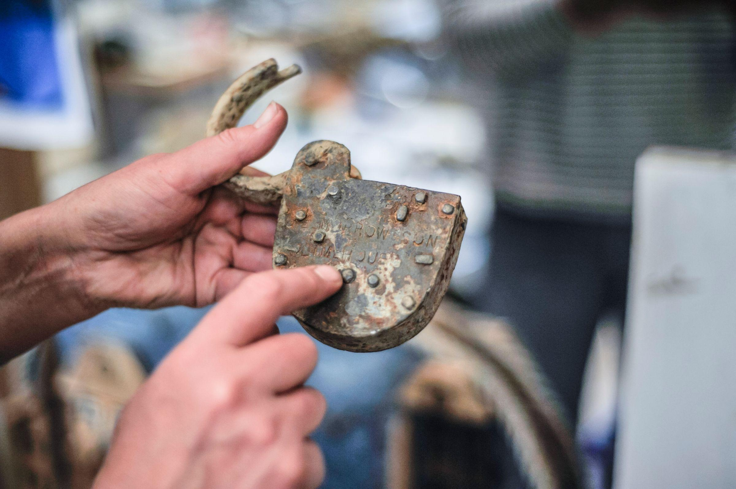 A man holding a rusted padlock