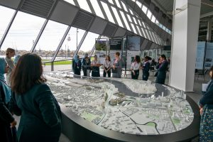A crowd around a model of the Royal Docks at The Crystal