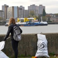 A woman with sacks of rubbish next to the river