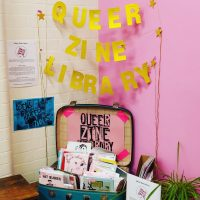 A display for Queer Zine Library in a suitcase