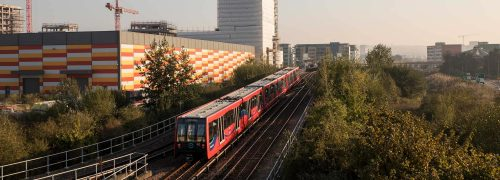 DLR train running between trees and building